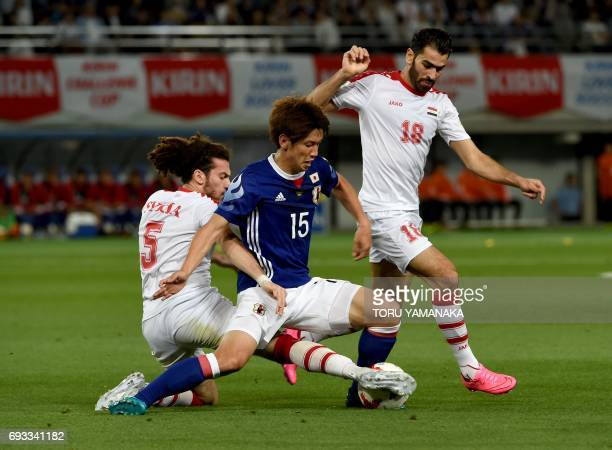 Japan's forward Yuta Osak battles for the ball with Syria's defender Omro Al Midani and midfielder Mhd Zahir Algunami Almedani during their friendly...