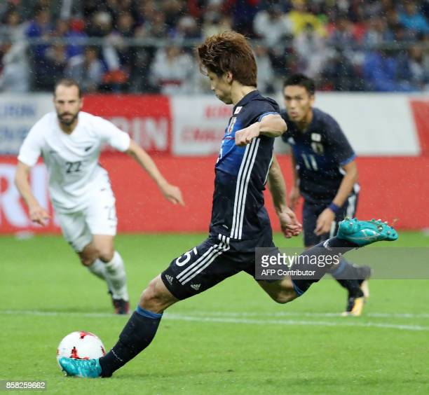 Japan's forward Yuya Osako scores a goal while a penalty kick during their friendly football match against New Zealand in Toyota city Aichi...