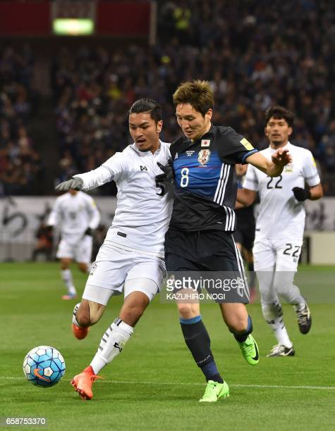 Japans Genki Haraguchi fights for the ball with Thailands Adison Promrak during group B World Cup 2018 qualifying football match between Japan and...