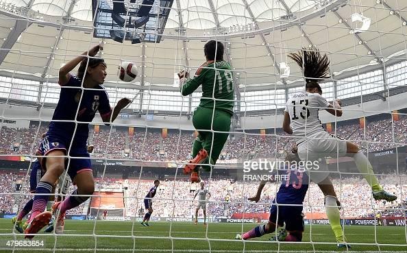 Japan's goalkeeper Ayumi Kaihori jumps for the ball next to USA forward Alex Morgan and Japan's defender Saki Kumagai during the final football match...