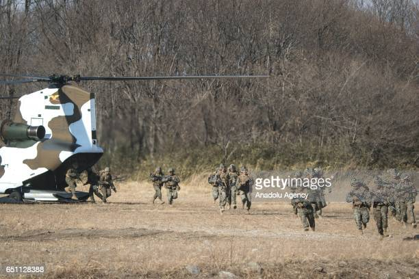 Japan's Ground Self Defense Force and the US Marines take up defensive position as they train in a joint training exercise in JGSDF grounds in Camp...