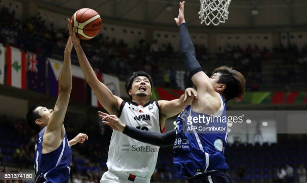 Japan's guard Takeuchi Kosuke attempts to score as he is marked by Korea's center Kim Jongkyu and forward Lim Dongseop during their 2017 FIBA Asia...