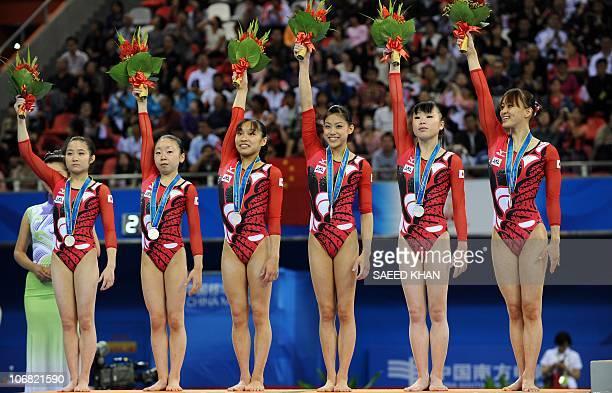 Japan's gymnasts Koko Tsurumi Mai Yamagishi Kyoko Oshima Yuko Shintake Momoko Ozawa and Rie Tanaka celebrate their silver medals on the podium during...