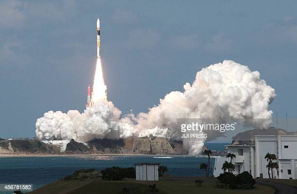 Japan's H2A rocket which carries the Himawari8 weather satellite leaves the launching pad at the Tanegashima Space Center Kagoshima prefecture in...