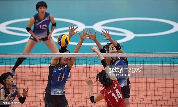 Japan's Haruka Miyashita and Japan's Yuki Ishii watch as Japan's Erika Araki and Japan's Saori Kimura jump to block a spike from South Korea's Yang...