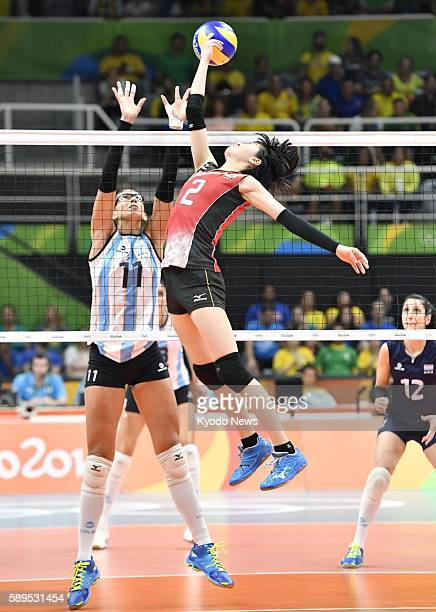 Japan's Haruka Miyashita taps the ball over the net as Argentina's Julieta Lazcano tries to block during the third set of their preliminaryround...