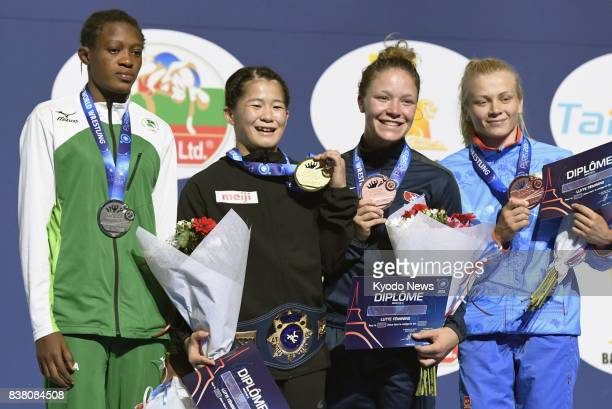 Japan's Haruna Okuno poses with her gold medal after winning the women's 55kilogram final at the world wrestling championships in Paris on Aug 23...