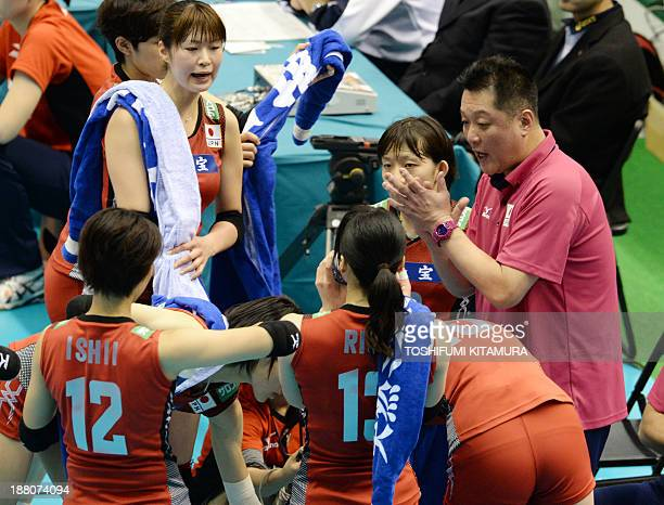 Japan's head coach Masayoshi Manabe speaks to his players during their FIVB volleyball women's Grand Champions Cup match against Thailand in Tokyo on...