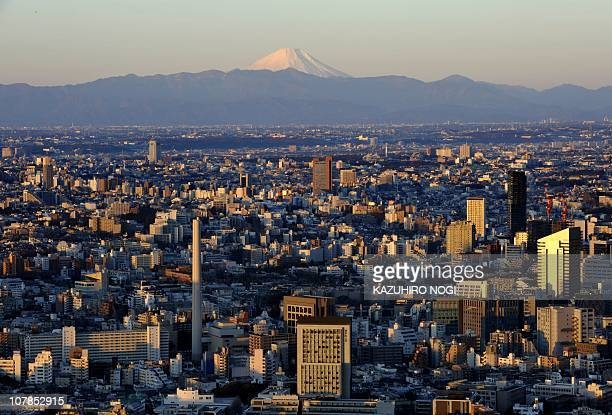 Japan's highest mountain Mount Fuji is seen above Japanese economic city of Tokyo during the sunrise on New Year's Day on January 1 2011 AFP...