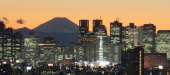 Japan's highest mountain Mt Fuji is seen in the background between skyscrapers in Tokyo's Shinjuku area during the sunset on January 7 2011 Japanese...