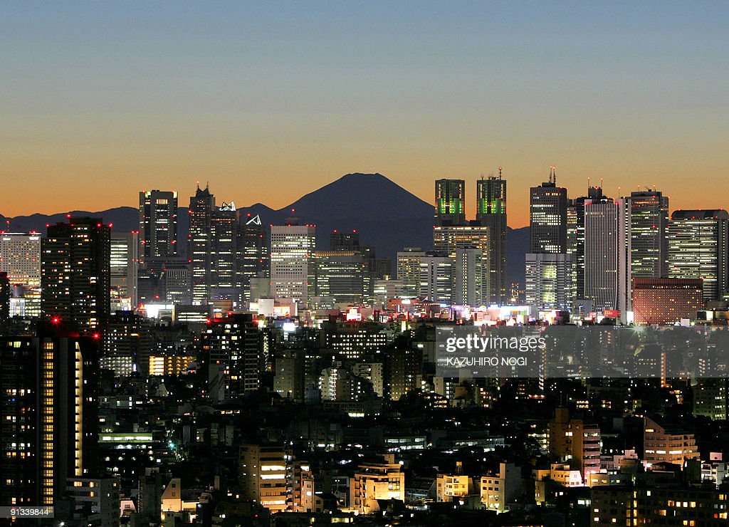 Japan's highest mountain Mt Fuji is seen in the background past skyscrapers rising above Japanese economic symbol Tokyo's Shinjuku area during sunset...
