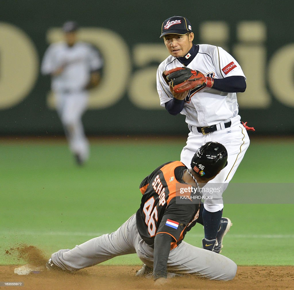 Japan's infielder Takashi Toritani (top) tries to get a double play over Netherlands' runner Jonathan Schoop during the 9th inning of the second-round Pool 1 game in the World Baseball Classic tournament at Tokyo Dome on March 12, 2013. Japan beat the Netherlands 10-6.
