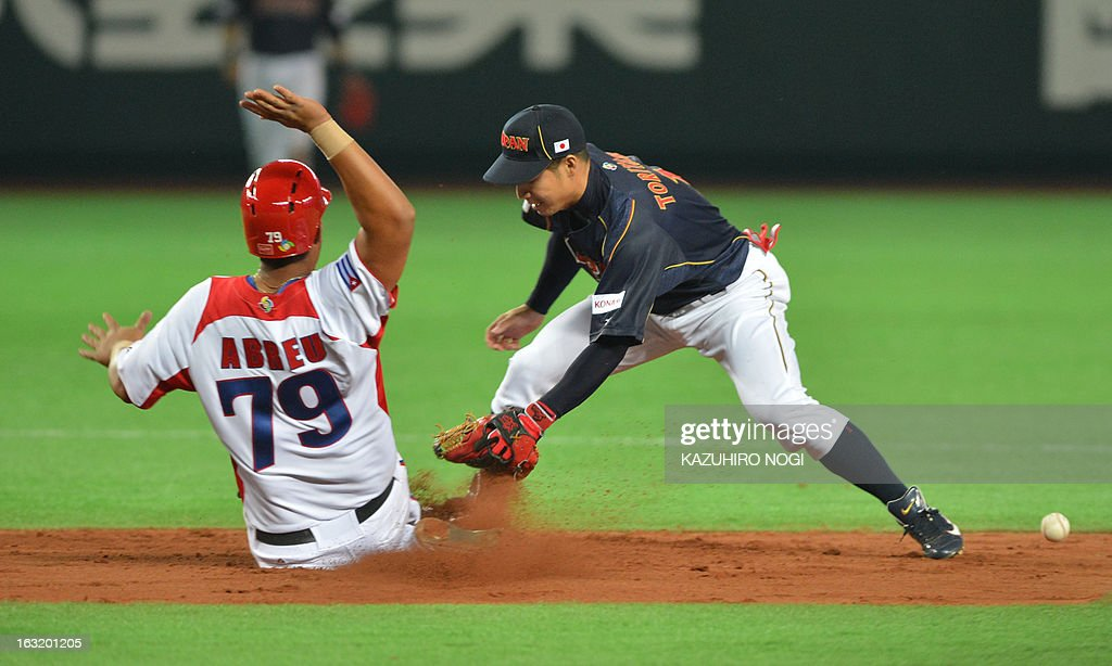 Japan's infielder Takashi Toritani (R) tries to tag out Cuba's Jose Abreu on the second base during the sixth inning of their first-round Pool A game in the World Baseball Classic tournament in Fukuoka on March 6, 2013.