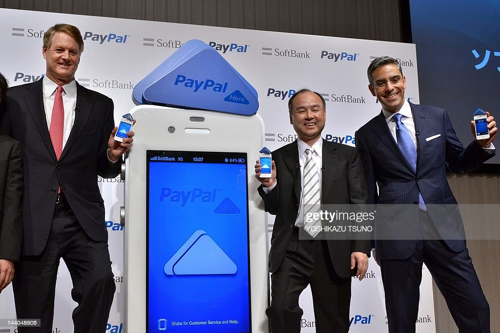 Japan's Internet giant Softbank president Masayoshi Son (C) and US online transaction giant eBay CEO John Donahoe (L) with eBay's subsidiary PayPal president David Marcus show their smartphones with triangle shaped dongles of credit card reader as they announce to form a joint venture to start online transaction service through the mobile Internet 'PayPal Here' in Tokyo on May 9, 2012. AFP PHOTO / Yoshikazu TSUNO