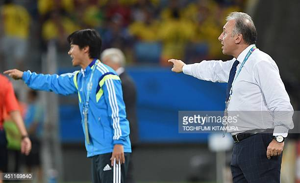 Japan's Italian coach Alberto Zaccheroni gestures to his team from the sideline during the Group C football match between Japan and Colombia at the...