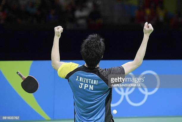 TOPSHOT Japan's Jun Mizutani celebrates beating China's Xu Xin in the singles match during their men's team gold medal table tennis match at the...