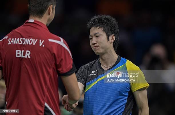 Japan's Jun Mizutani greets Belarus' Vladimir Samsonov after winning their men's singles bronze medal table tennis match at the Riocentro venue...