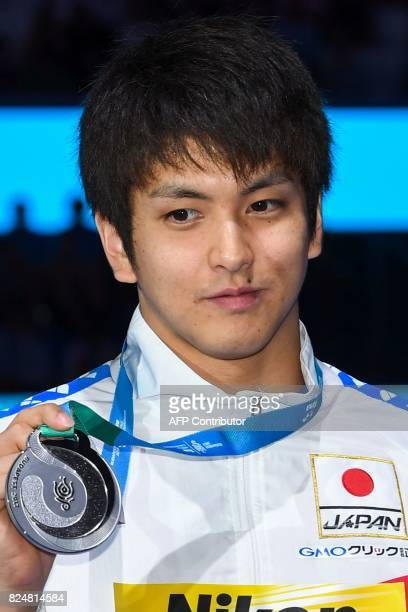 Japan's Junya Koga poses with his gold medal on the podium of the men's 50m backstroke during the swimming competition at the 2017 FINA World...