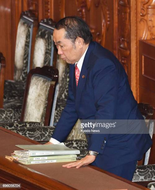 Japan's Justice Minister Katsutoshi Kaneda bows his head in appreciation as a plenary session of the House of Councillors enacted contentious...