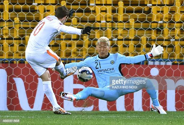 Japan's Kashiwa Reysol goalkeeper Takanori Sugeno tries to block a shot by China's Shandong Luneng FC forward Walter Montillo during their AFC...