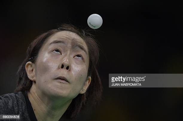 Japan's Kasumi Ishikawa eyes the ball as she serves in the women's team bronze medal table tennis match against Singapore at the Riocentro venue...