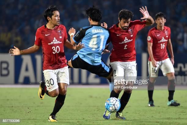 Japan's Kawasaki Frontale midfielder Akihiro Ienaga fights for the ball with Japan's Urawa Reds forward Shinzo Koroki and defender Mauricio de...