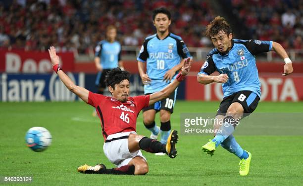 Japan's Kawasaki Frontale midfielder Hiroyuki Abe shoots past Urawa Reds defender Ryota Moriwaki fights for the ball with during the AFC Champions...