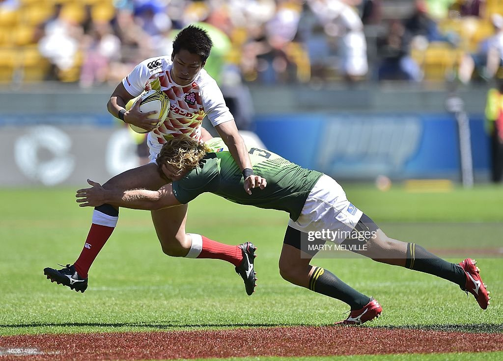 Japan's Kazushi Hano is tackled by South Africa's Werner Kok on day one of the IRB International Sevens rugby tournament at Westpac Stadium in...