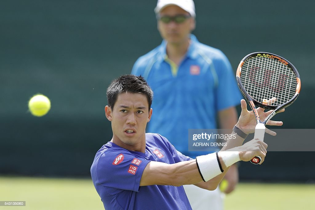 Japan's Kei Nishikori (front) plays a shot on a practice court under the watch of his US coach Michael Chang (back) at The All England Tennis Club in Wimbledon, southwest London, on June 26, 2016, on the eve of the start of the 2016 Wimbledon Championships tennis tournament. / AFP / ADRIAN