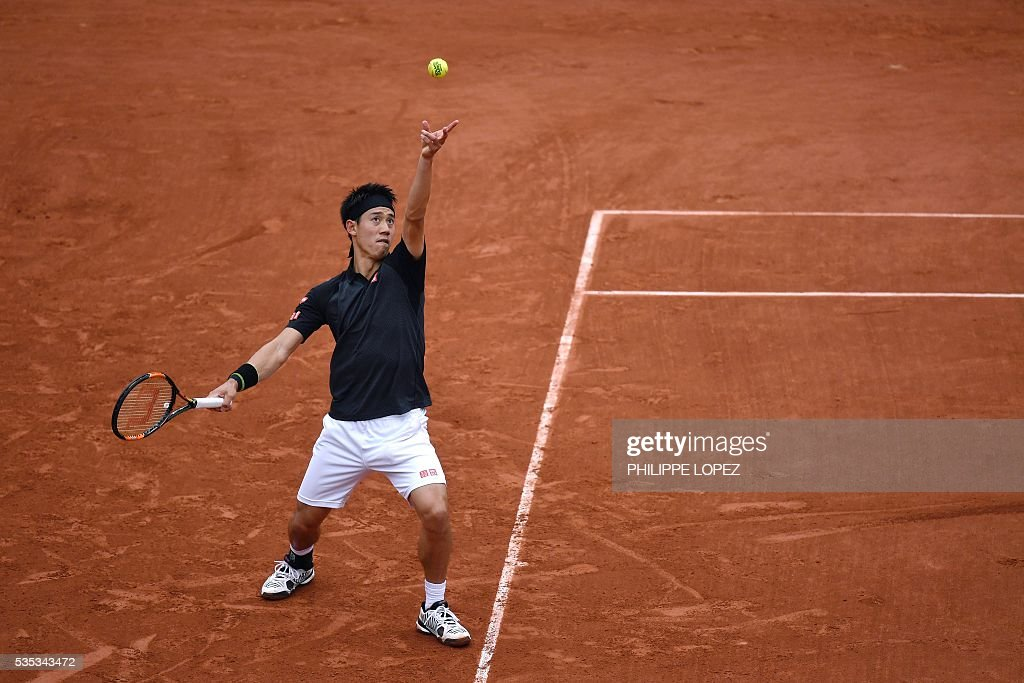 Japan's Kei Nishikori serves the ball to France's Richard Gasquet during their men's fourth round match at the Roland Garros 2016 French Tennis Open in Paris on May 29, 2016. / AFP / PHILIPPE