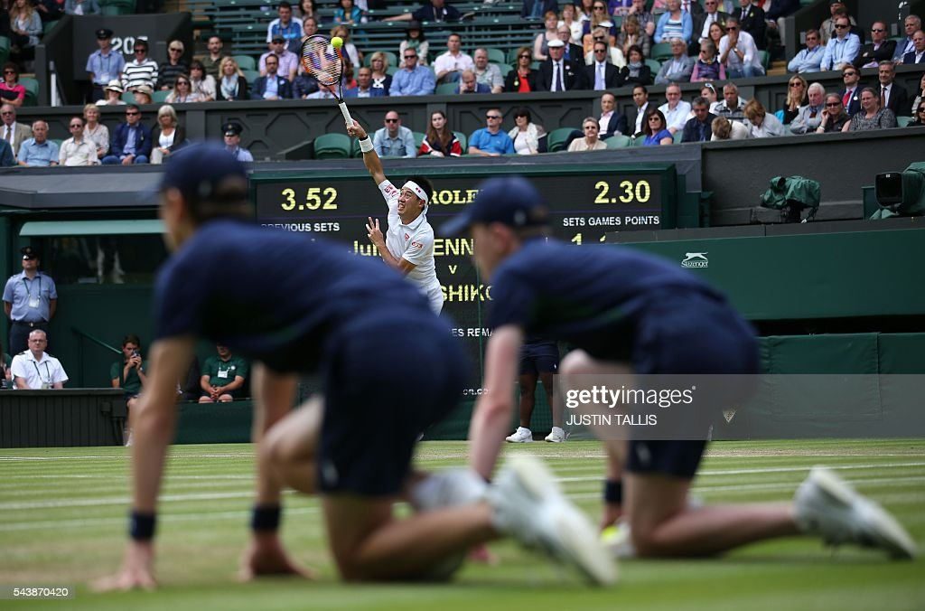 Japan's Kei Nishikori serves to France's Julien Benneteau during their men's singles second round match on the fourth day of the 2016 Wimbledon Championships at The All England Lawn Tennis Club in Wimbledon, southwest London, on June 30, 2016. / AFP / JUSTIN