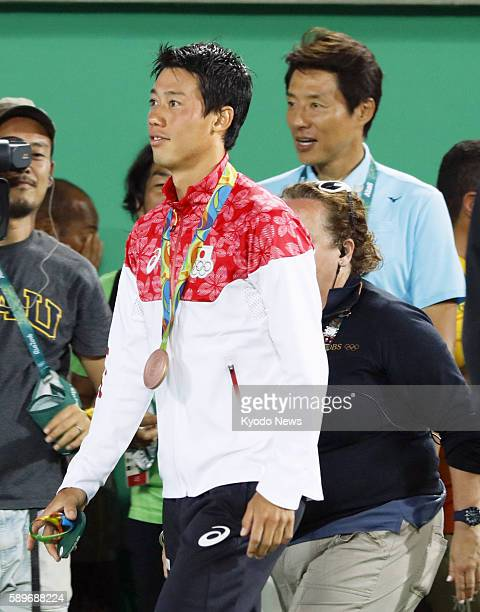 Japan's Kei Nishikori stands with his bronze medal with tennis commentator Shuzo Matsuoka in the background at the medal ceremony for the Rio de...
