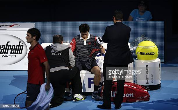 Japan's Kei Nishikori takes a medical timeout during his Group B singles match against Switzerland's Roger Federer on day three of the ATP World Tour...