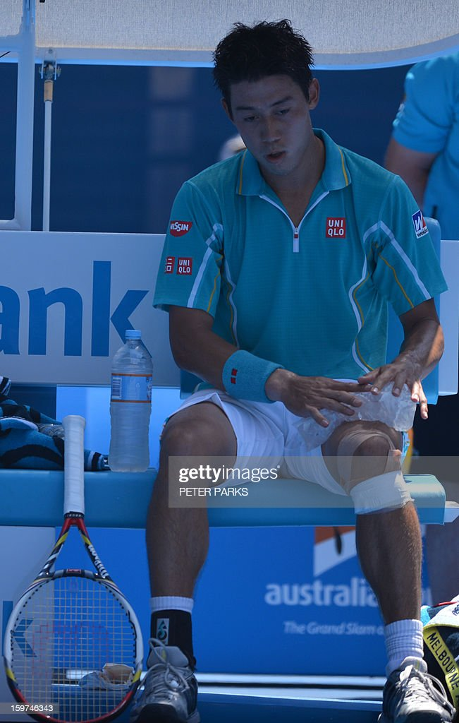 Japan's Kei Nishikori uses an ice-pack during his men's singles match against Spain's David Ferrer on the seventh day of the Australian Open tennis tournament in Melbourne on January 20, 2013. AFP PHOTO/PETER PARKS IMAGE STRICTLY RESTRICTED TO EDITORIAL USE - STRICTLY NO COMMERCIAL USE