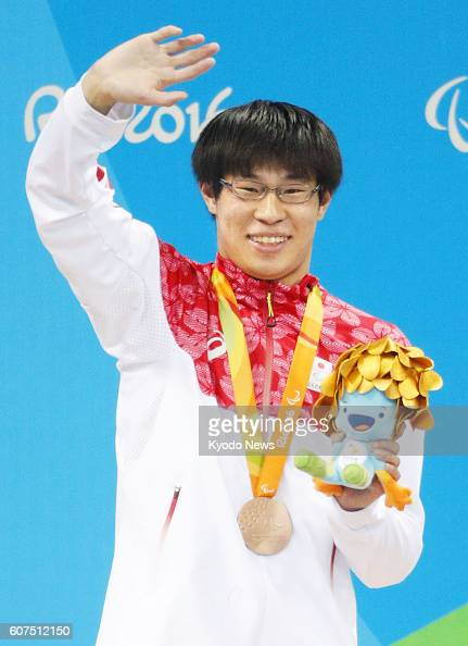Japan's Keichi Nakajima waves to the crowd from the podium after winning the bronze medal in the men's 200meter individual medley in the SM14 class...