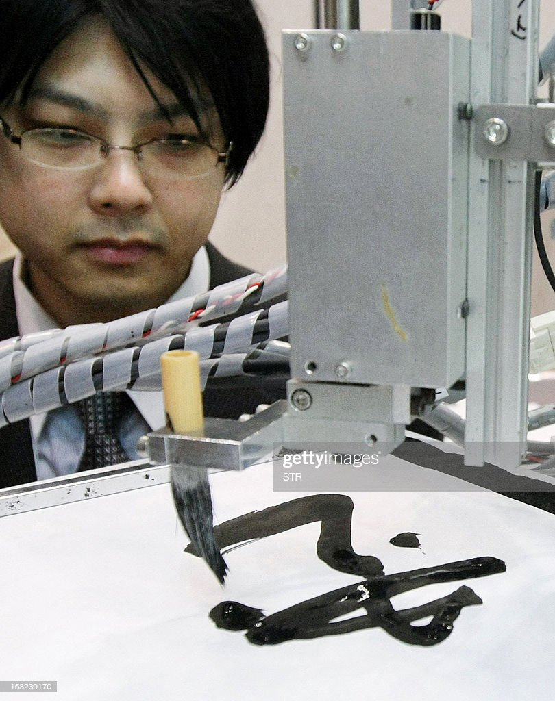 Japan's Keio University associate professor Seiichiro Katsura demonstrates a robot (R) that can mimic the exact brush strokes of master painters or calligraphers at Asia's largest electronics trade show, the Combined Exhibition of Advanced Technologies (CEATEC) exhibition at Chiba, suburban Tokyo on October 2, 2012. A perfect copy of a work by long-dead artists such as Monet or Picasso is not possible, as the robot needs a living model to imitate, applying the same pressure and making the same gestures, Katsura said. JAPAN