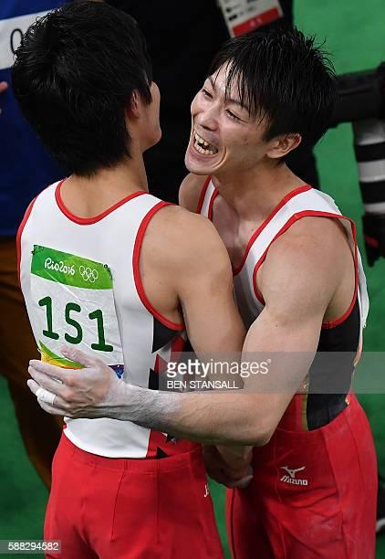 Japan's Kohei Uchimura celebrates with Japan's Ryohei Kato after winning the men's individual allaround final of the Artistic Gymnastics at the...