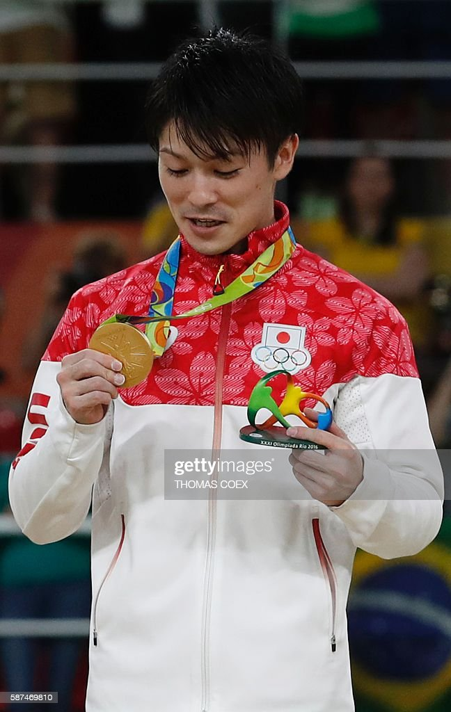 Japan's Kohei Uchimura looks at his gold medal on the podium of the men's team final of the Artistic Gymnastics at the Olympic Arena during the Rio 2016 Olympic Games in Rio de Janeiro on August 8, 2016. / AFP / Thomas COEX