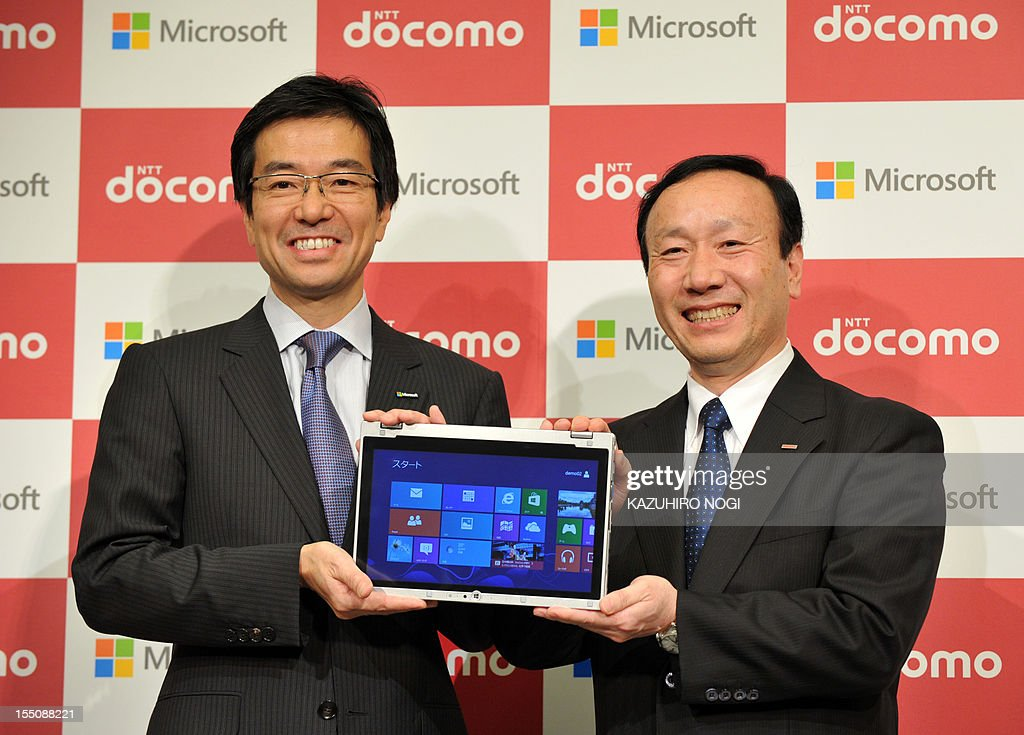 Japan's leading mobile operator NTT DOCOMO president Kaoru Kato (R) and Microsoft Japan president Yasuyuki Higuchi hold a Windows 8 tablet during their joint press conference in Tokyo on November 1, 2012. Microsoft Japan and NTT DOCOMO announced they have agreed on a cooperative business relationship to combine Windows 8 tablet devices and DOCOMO's extra-high-speed LTE mobile service, Xi (read 'crossy'), for corporate users in Japan. AFP PHOTO / KAZUHIRO NOGI