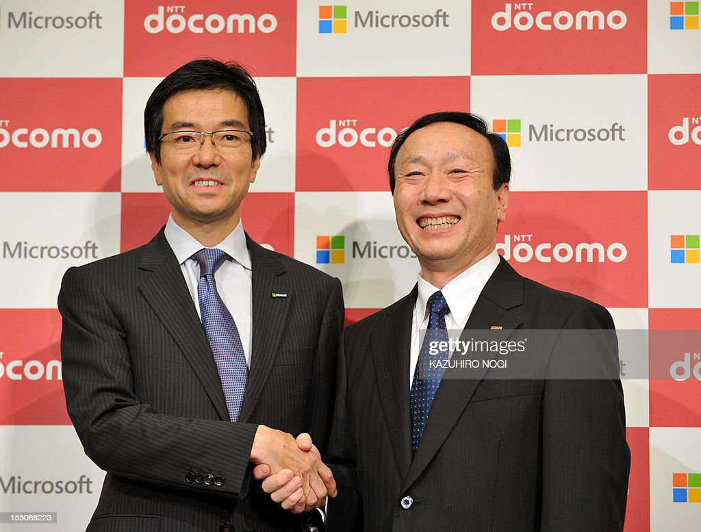Japan's leading mobile operator NTT DOCOMO president Kaoru Kato (R) shakes hands with Microsoft Japan president Yasuyuki Higuchi after their joint press conference in Tokyo on November 1, 2012. Microsoft Japan and NTT DOCOMO announced they have agreed on a cooperative business relationship to combine Windows 8 tablet devices and DOCOMO's extra-high-speed LTE mobile service, Xi (read 'crossy'), for corporate users in Japan.