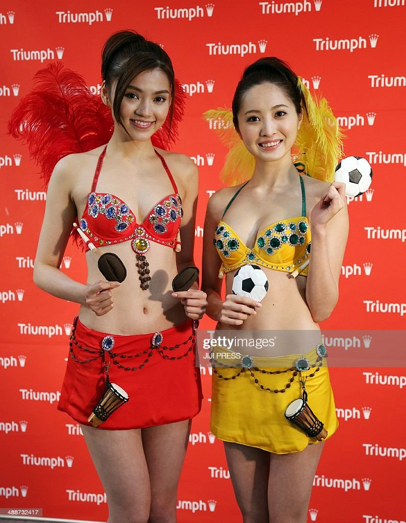 Japan's lingerie maker Triumph International Japan campaign models Ai Takahara (L) and Eri Oishi (R) display the new unique bra 'Brazil passion bra' in Tokyo on May 8, 2014, ahead of the upcoming Brazil World Cup. The unique bra has coffee bean shaped pads and feather decorations that are attached on its back.