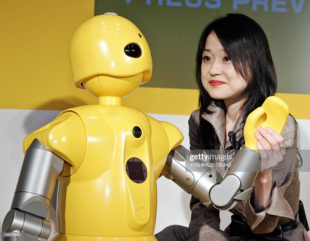 Japan's machinery maker Mitsubishi Heavy Industries employee displays the company's humanoid robot 'Wakamaru' which enables to recognize human faces...