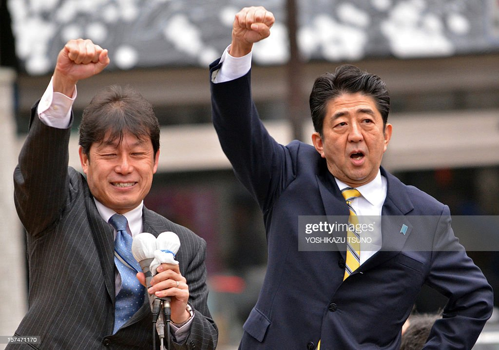 Japan's main opposition Liberal Democratic Party (LDP) leader Shinzo Abe (R) raises his fist alongside a LDP member (L) in support of his party's candidate Yoshitami Kameyama at Fukushima, northern Japan on December 4, 2012. Campaigning officially started ahead of Japan's December 16 general election. AFP PHOTO / Yoshikazu TSUNO
