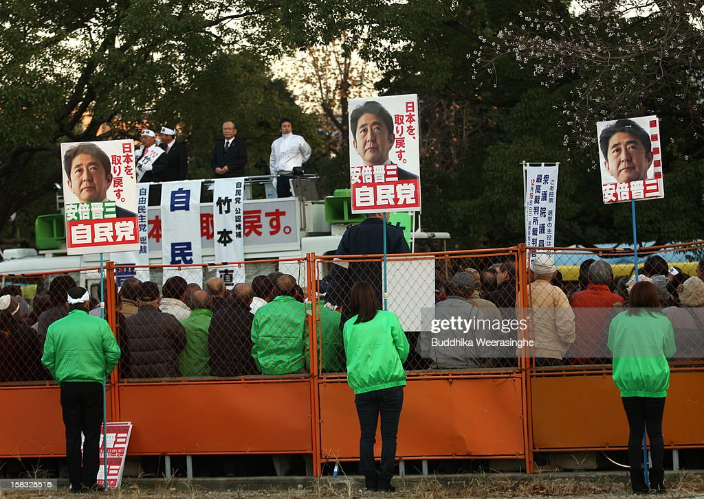 Japan's main opposition Liberal Democratic Party (LDP) supporters hold up placards in support of party leader its leader Shinzo Abe's during party election campaign on December 13, 2012 in Osaka, Japan. Japanese voters will go to the polls for a general election on December 16, 2012.