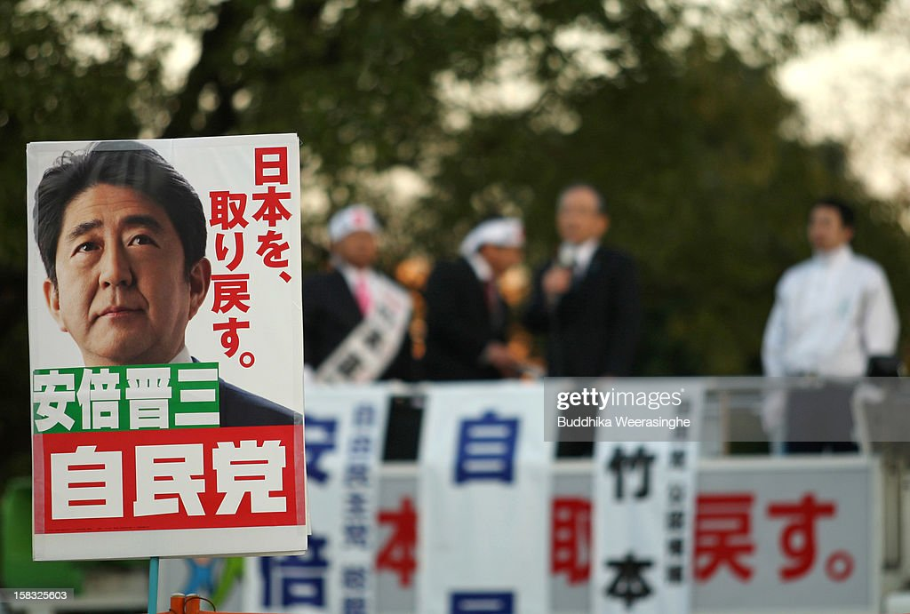Japan's main opposition Liberal Democratic Party (LDP) supporters hold up placards in support of party leader its leader Shinzo Abe during his party election campaign on December 13, 2012 in Osaka, Japan. Japanese voters will go to the polls for a general election on December 16, 2012.