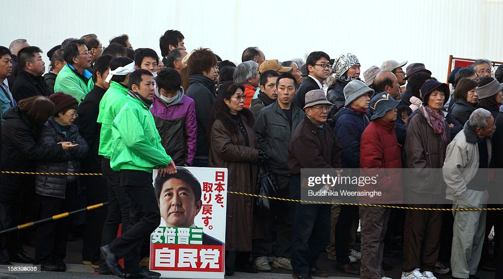 Japan's main opposition Liberal Democratic Party (LDP) supporters with placards in support of its leader Shinzo Abe during his party election campaign on December 13, 2012 in Osaka, Japan. Japanese voters will go to the polls for a general election on December 16, 2012.