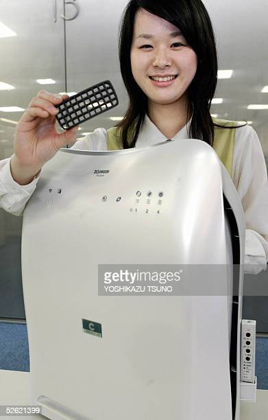 Japan's major vacum bottles and cooking appliances maker Zojirushi employee displays the company's air purifier 'Air Breeze' and its vitamin C...