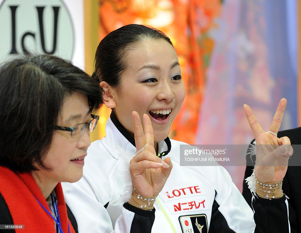 Japan's Mao Asada (R) flashes victory signs after her ladies free skating performance at the Four Continents figure skating championships in Osaka, February 10, 2013. AFP PHOTO / TOSHIFUMI KITAMURA