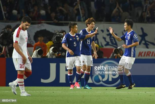 Japan's midfiedler Yasuyuki Konno is celebrated by his teammate Yuto Nagatomo and Yuta Osako during a friendly football match between Japan and Syria...