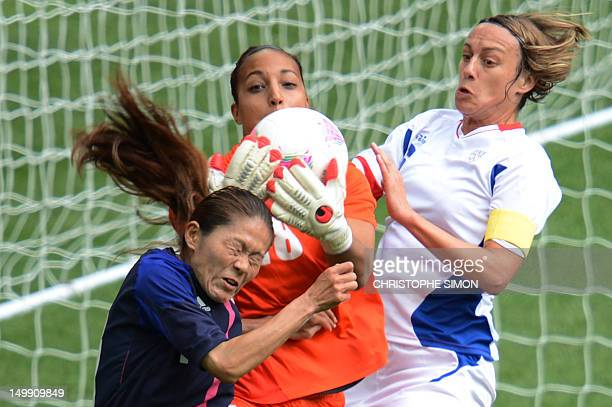 Japan's midfielder Homare Sawa fights for the ball with France's goalkeeper Sarah Bouhaddi and France's Sandrine Soubeyrand during their women's...